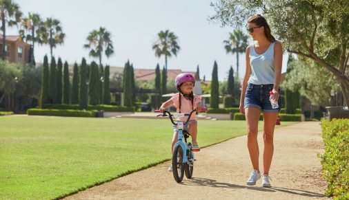Exterior view of young girl riding bike with mother at Los Olivos Apartment Homes in Irvine, CA.