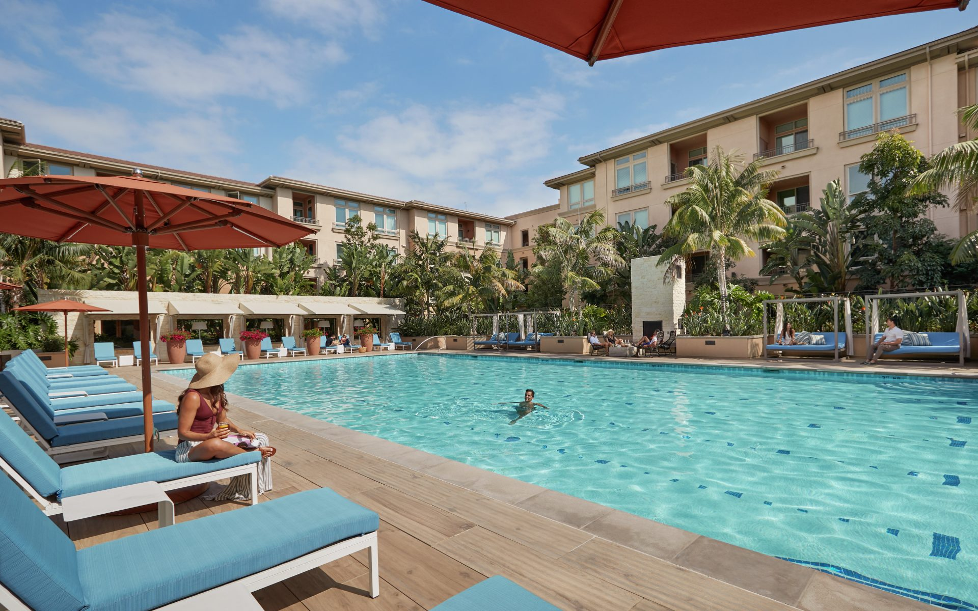 Exterior view of people spending time by pool at Villas at Playa Vista Apartment Homes in Playa Vista, CA.