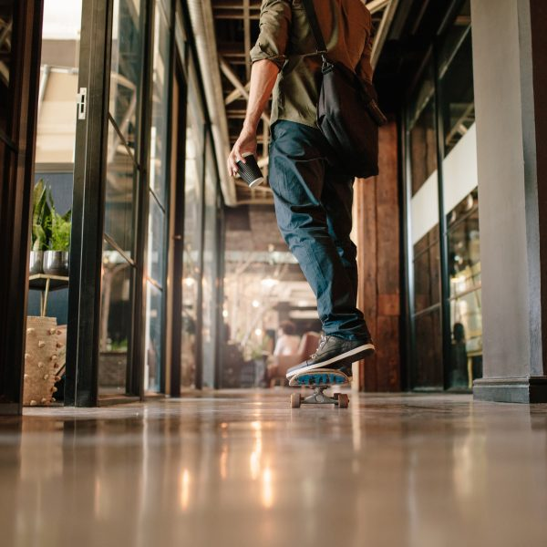 Low angle rear view shot of casual man skateboarding in office. Young businessman skating through his startup office.